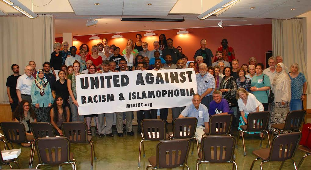 """conference attendees gather around sign """"United Against Racism & Islamophobia"""""""