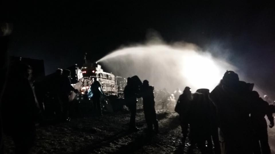 nighttime photo of police spraying water over protesters in sub-zero temps