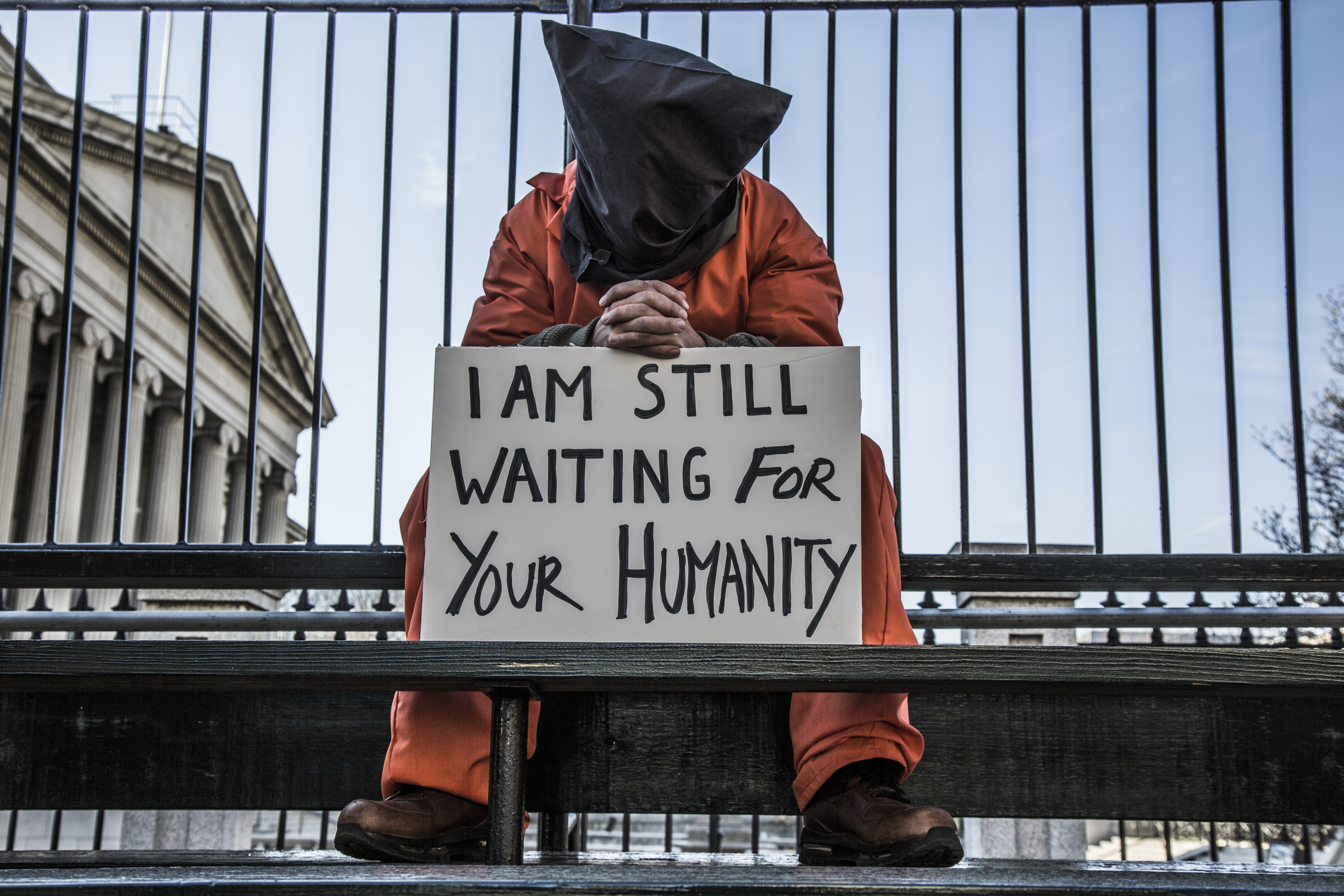 """protester dressed in hood an orange jumpsuit with sign """"I am still waiting for your humanity"""" in front of the white house"""