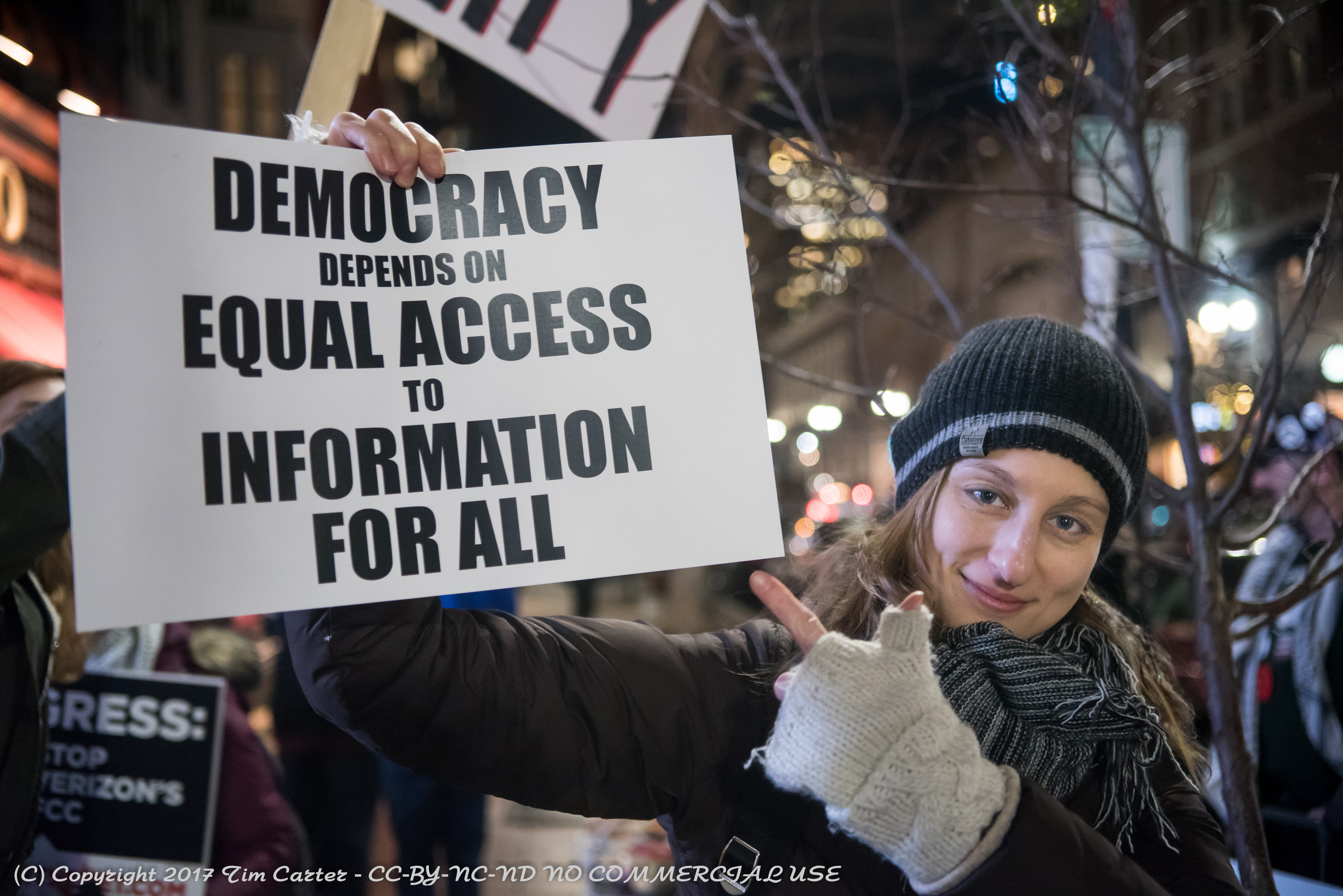 """Woman holding sign """"Democracy requires equal access to information for all"""""""