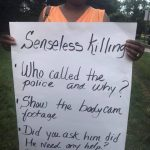 Black Woman holds sign asking who called the police and why??