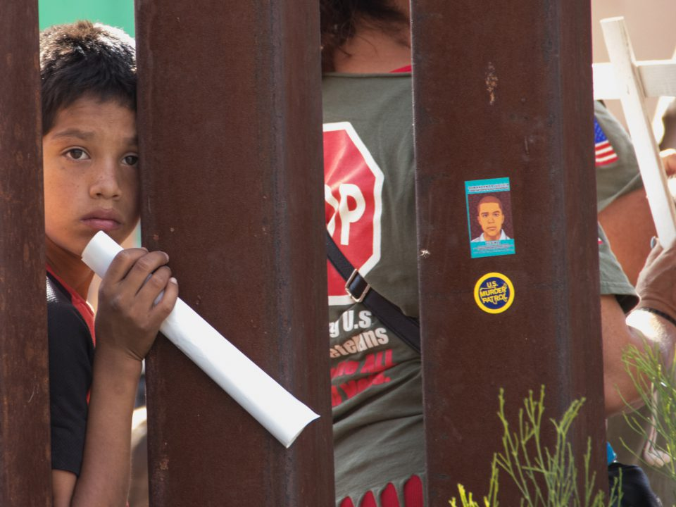 child looks through border wall