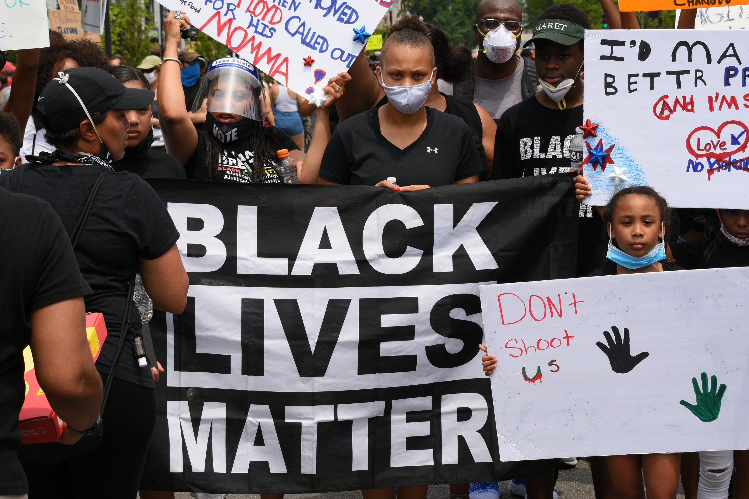 young Black people at Black Lives Matter protest with sign and facemasks